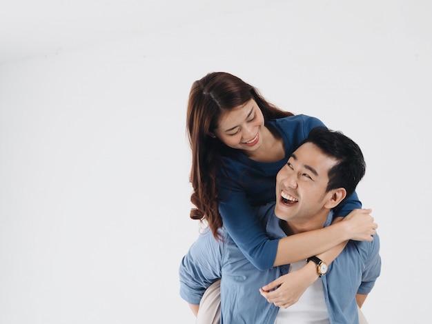 Gelukkige aziatische mens die zijn meisje op de rug over witte achtergrond, exemplaarruimte vervoert.