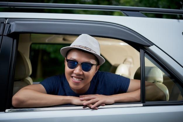 Gelukkige aziatische mens in hoed en zonnebril die bij achterruit van auto stellen