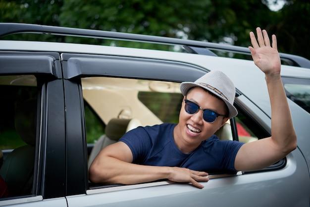 Gelukkige aziatische mens in hoed en zonnebril die uit achterruit van auto en het golven leunen