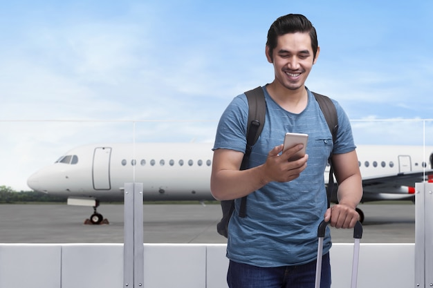 Gelukkige aziatische mensenreiziger die zich met zak en mobiele telefoon bevinden