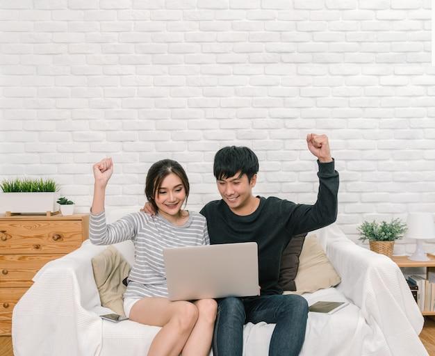Gelukkige aziatische minnaar die en de digitale laptop in vrolijke actie over de bank zitten gebruiken