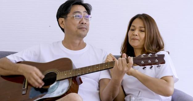 Gelukkige aziatische minnaar die gitaar speelt en liedjes samen in een ruimte zingt.