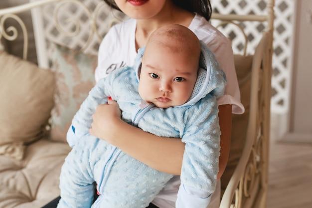 Gelukkige aziatische moeder die aanbiddelijk kindbabyjongen houdt.