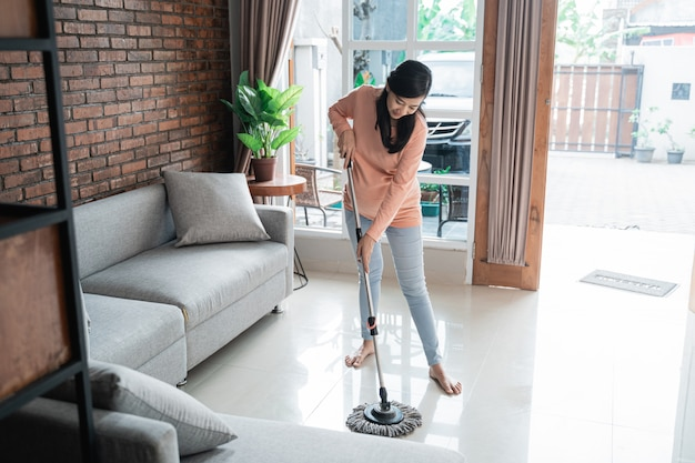 Gelukkige aziatische moeder die de vloer met zwabber schoonmaakt