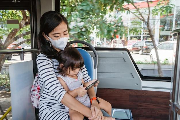 Gelukkige aziatische moeder die haar dochter meeneemt in het openbaar vervoer