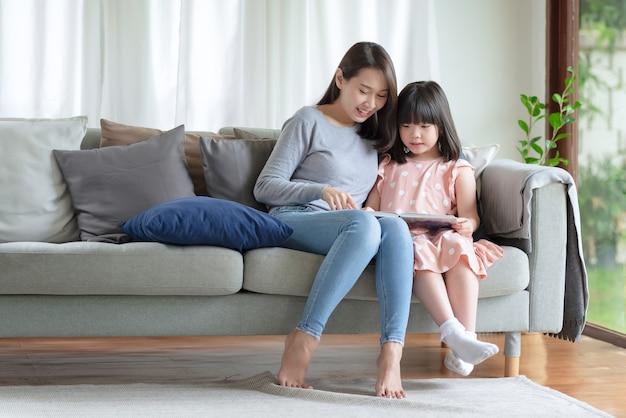 Gelukkige aziatische moeder die haar schattige dochter leert om thuis in de woonkamer te studeren