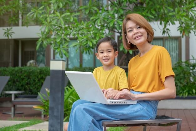 Gelukkige aziatische moeder die haar zoon voor gebruikslaptop computer onderwijzen bij openlucht