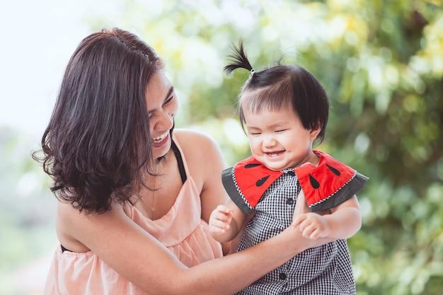Gelukkige aziatische moeder en het leuke kleine babymeisje die samen met pret en liefde spelen