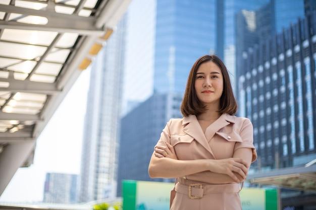 Gelukkige aziatische mooie bedrijfsvrouw openlucht