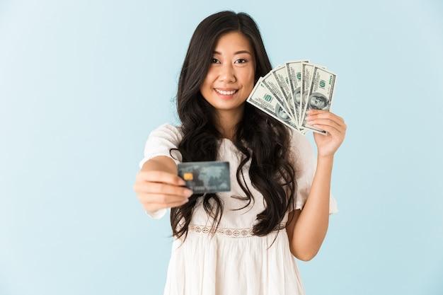 Gelukkige aziatische mooie vrouw die over de blauwe creditcard en het geld van de muurholding wordt geïsoleerd