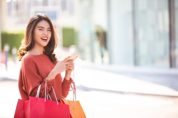 Gelukkige aziatische mooie vrouwenholding het winkelen zakken terwijl het gebruiken van smartphone