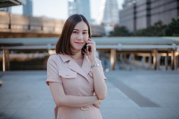 Gelukkige aziatische mooie zakenvrouw buiten