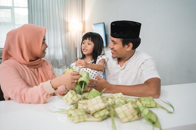 Gelukkige aziatische moslimfamilie die ketupat samen thuis vóór eid mubarak maakt