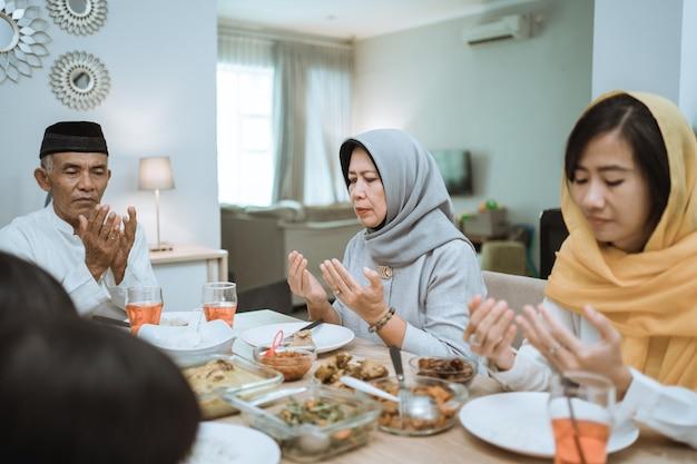 Gelukkige aziatische moslimfamilie die vóór hun iftarmaaltijd bidt tijdens het vasten van de ramadan