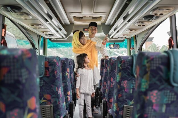 Gelukkige aziatische moslimvakantiereis die samen met familie een bus berijdt