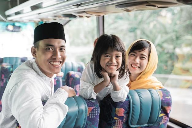 Gelukkige aziatische moslimvakantiereis samen met familie in een bus rijden