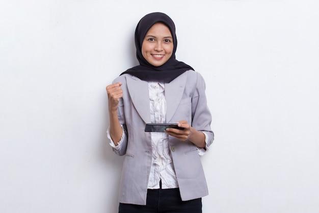 Gelukkige aziatische moslimvrouw enthousiast om spelletjes te spelen op haar smartphone