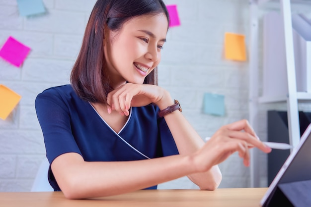 Gelukkige aziatische onderneemster die aan tablet bij de lijst in huisbureau werken.