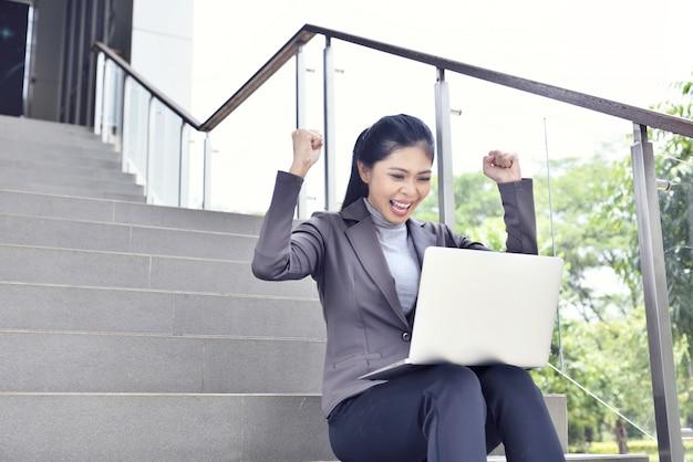 Gelukkige aziatische onderneemster met laptop het werken