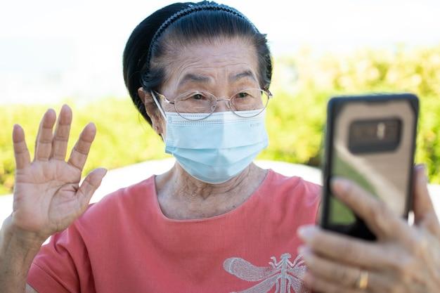 Gelukkige aziatische ouderen die een gezichtsmasker dragen en een videogesprek beantwoorden met haar smartphone in het park en chatten met familie, technologie en ouderenconcept.