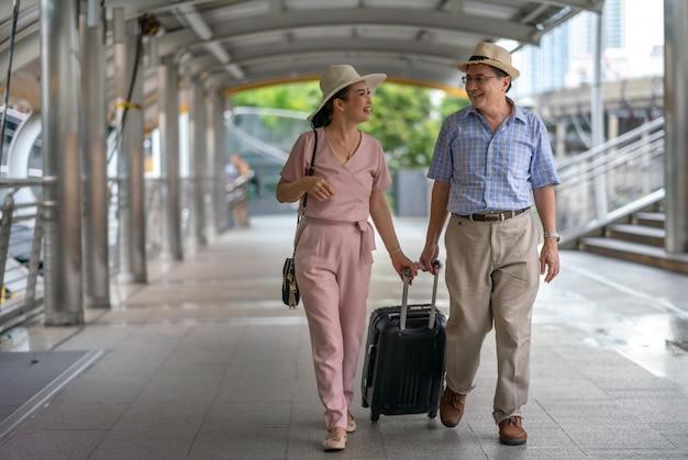 Gelukkige aziatische paar hogere toeristen die kofferhandvat in de stad houden terwijl het reizen