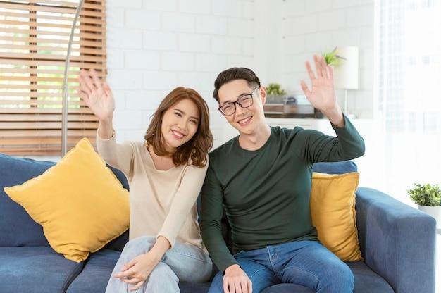 Gelukkige aziatische paar man en vrouw video-oproep virtuele bijeenkomst samen op de bank thuis woonkamer.