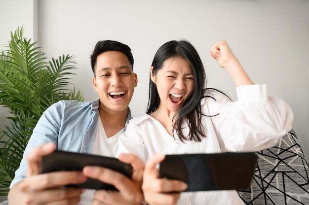 Gelukkige aziatische paar plezier speelspel in smartphone mobiel in de woonkamer
