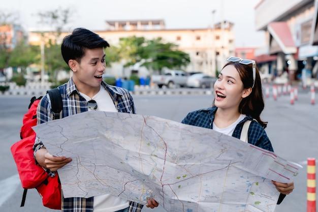 Gelukkige aziatische paar toeristische backpackers die een papieren kaart vasthouden en op zoek zijn naar richting tijdens het reizen, ze glimlachen blij wanneer ze op de locatie op de papieren kaartbestemming zijn aangekomen.