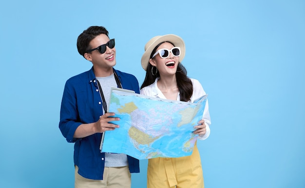 Gelukkige aziatische paartoerist die de kaart openen om op zomervakantie te reizen die op blauwe achtergrond wordt geïsoleerd.