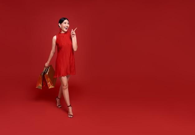 Gelukkige aziatische shopaholic vrouw die traditionele cheongsam qipao-kledingshand draagt die omhoog wijst om ruimte te kopiëren die op rode achtergrond wordt geïsoleerd. gelukkig chinees nieuwjaar