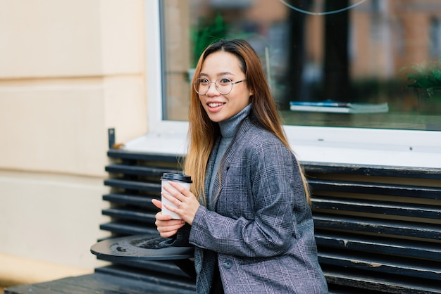 Gelukkige aziatische studente op de stadsstraat, onderwijsconcept