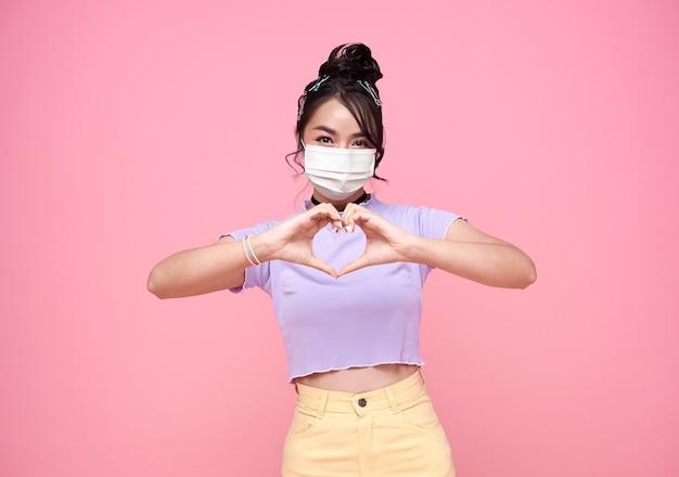 Gelukkige aziatische tiener vrouw hand die mini hart toont en gezichtsmasker draagt dat beschermt tegen corovavirus over roze achtergrond. gezondheidszorg en beschermend concept.