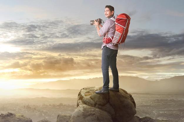 Gelukkige aziatische toerist met camera en rugzak klaar om een foto te nemen