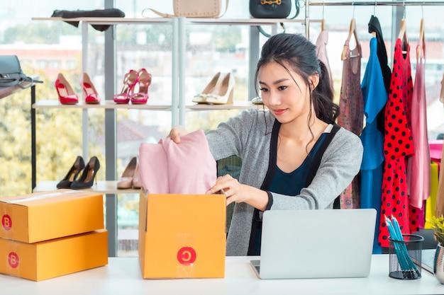 Gelukkige aziatische toevallige dame werkende start kleine bedrijfsondernemer kmo in klerenwinkel.