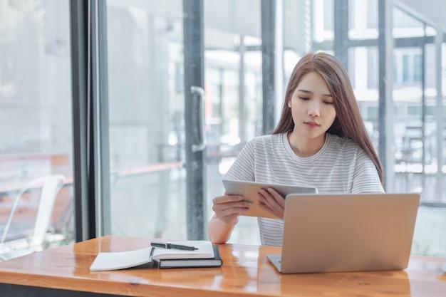 Gelukkige aziatische universitaire studenten die en aan tabletcomputer zitten werken in bibliotheek, die voor examens voorbereidingen treffen.