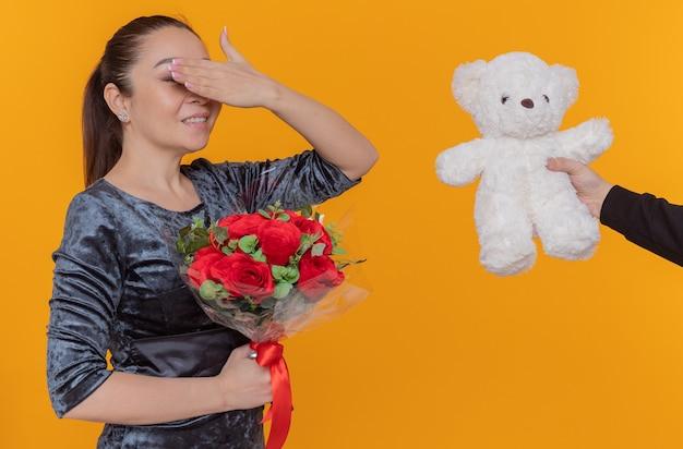 Gelukkige aziatische vrouw die blij en verrast kijkt die ogen bedekt met hand die teddybeer ontvangt als een geschenk glimlachend vrolijk terwijl ze internationale vrouwendag viert die zich over oranje muur bevindt