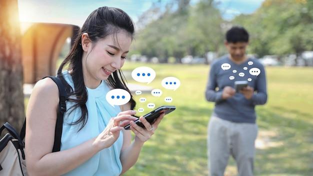 Gelukkige aziatische vrouw die buiten staat met smartphone in de buurt, staat man aan het typen op mobiele telefoon met sociale media-interactie, bericht met meldingspictogrammen, commentaar boven apparaat. lifestyle met technologie