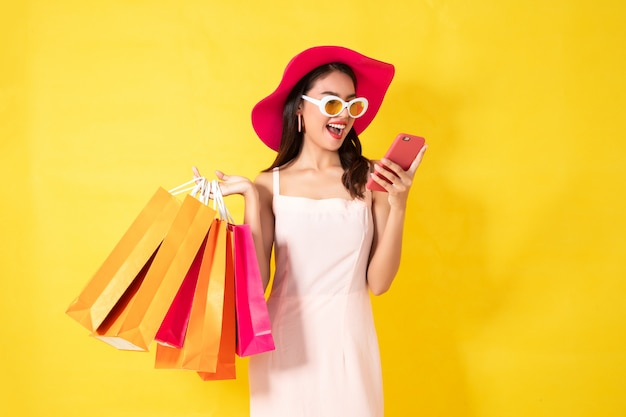 Gelukkige aziatische vrouw die celtelefoon op gele achtergrond met behulp van, kleurrijk het winkelen concept.