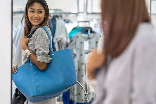 Gelukkige aziatische vrouw die de winkel voor damestassen kiest met vrolijke actie