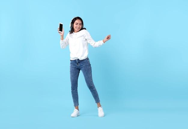 Gelukkige aziatische vrouw die draadloze hoofdtelefoon draagt die aan muziek van smartphone op blauw luistert.