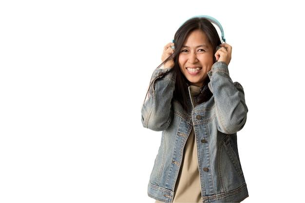 Gelukkige aziatische vrouw die draadloze hoofdtelefoons draagt die aan muziek luisteren, isoleren op witte achtergrond.