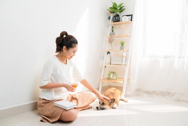 Gelukkige aziatische vrouw die een boek leest en op de vloer zit met haar zwarte hond thuis, lifestyle concept.