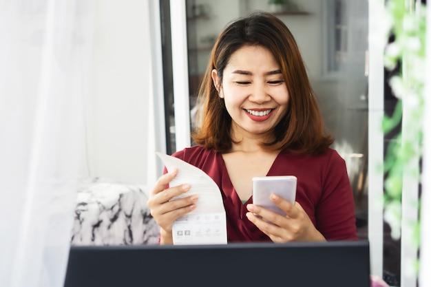Gelukkige aziatische vrouw die elektriciteitsrekening betaalt door slimme telefoon