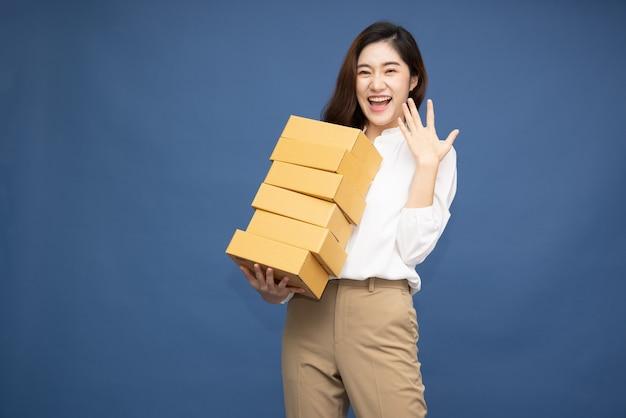 Gelukkige aziatische vrouw die en de doos van het pakketpakket glimlacht houdt die op diepblauwe oppervlakte wordt geïsoleerd.