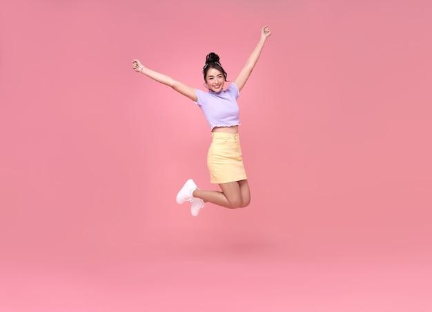 Gelukkige aziatische vrouw die en terwijl het vieren van succes glimlacht springt dat over roze achtergrond wordt geïsoleerd.