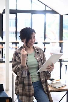 Gelukkige aziatische vrouw die goed nieuws ontvangt en haar succes viert.