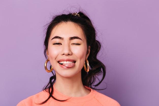 Gelukkige aziatische vrouw die grappige gezichten maakt. vooraanzicht van trendy japanse jonge vrouw in oorbellen.