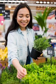 Gelukkige aziatische vrouw die groen in kruidenierswinkelopslag kiezen