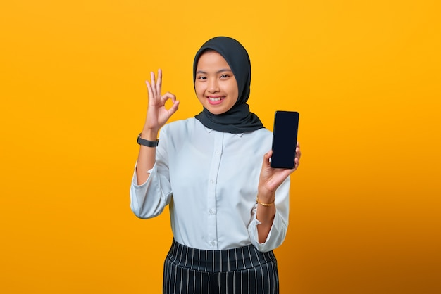 Gelukkige aziatische vrouw die het lege scherm van de mobiele telefoon en het handgebaar oke op gele achtergrond toont