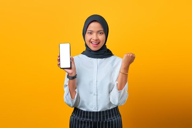 Gelukkige aziatische vrouw die het lege scherm van de mobiele telefoon en het succes van het handgebaar op gele achtergrond toont